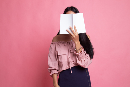 Young Asian woman with a book cover her face on pink background