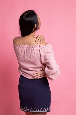 Young Asian woman got back pain on pink background