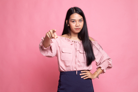 Young Asian woman angry and point to camera on pink background Banco de Imagens