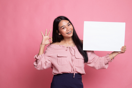 Young Asian woman show OK with  white blank sign on pink background