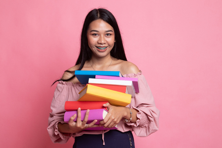 Young Asian woman studying  with may books on pink background