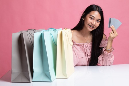 Young Asian woman with shopping bag and blank card on pink background