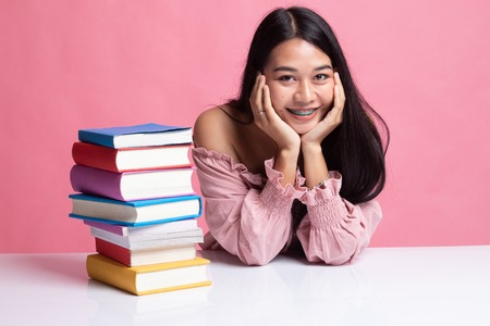Young Asian woman read a book with books on table on pink background Zdjęcie Seryjne - 122487564