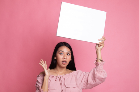 Young Asian woman surprise with white blank sign on pink background 版權商用圖片