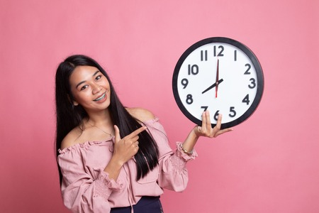 Young Asian woman point to a clock on pink background
