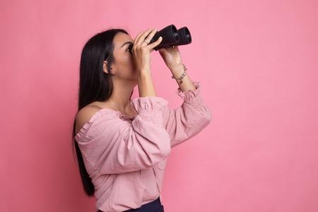 Jonge Aziatische vrouw met verrekijker op roze background
