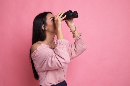Young Asian woman with binoculars on pink background Foto de archivo