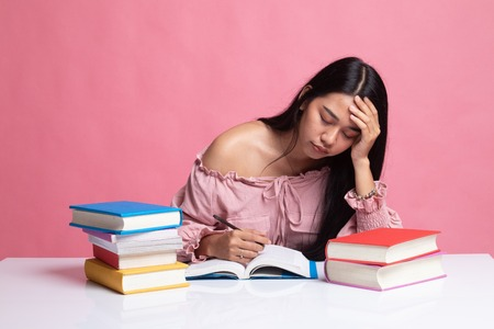 Exhausted Young Asian woman read a book with books on table on pink background