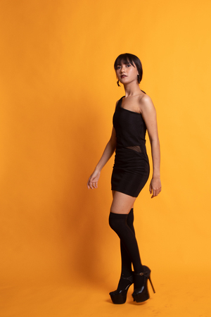 Full body of beautiful young asian woman on yellow background 写真素材