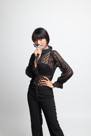 Portrait of beautiful young asian woman singer sing with microphone on white background