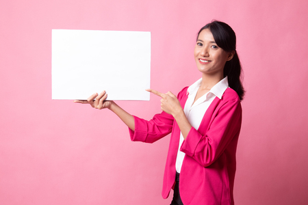 Young Asian woman point to  blank sign on pink background
