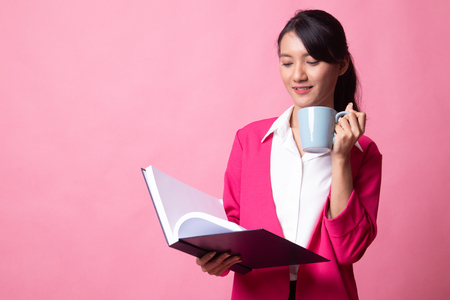 Young Asian woman with a book and cup of coffee on pink background Stockfoto
