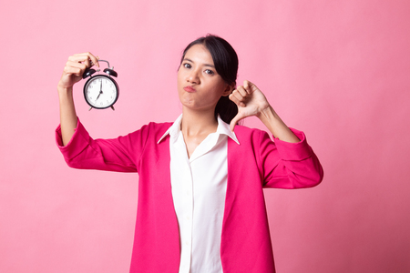 Young Asian woman thumbs down with a clock on pink background