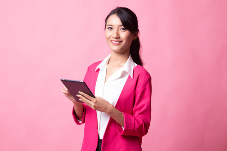 Young Asian woman with a computer tablet on pink background