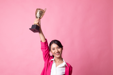 Successful young asian woman holding a trophy on pink background Imagens - 122811483