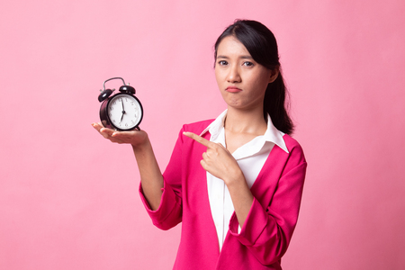 Angry young Asian woman point to a clock on pink background