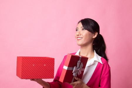 Young Asian woman open a gift box on pink background 版權商用圖片