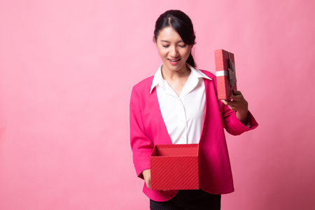 Young Asian woman open a gift box on pink background Stock Photo