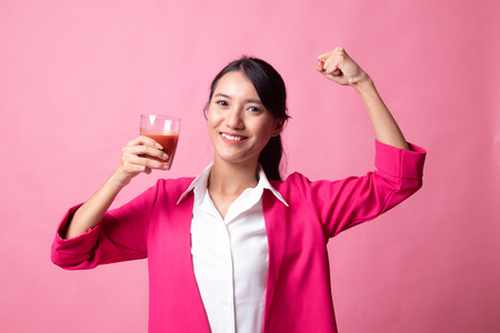 Strong healthy Asian woman with tomato juice on pink background