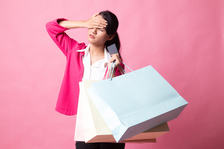 Unhappy  young Asian woman with shopping bags and credit card on pink background Standard-Bild
