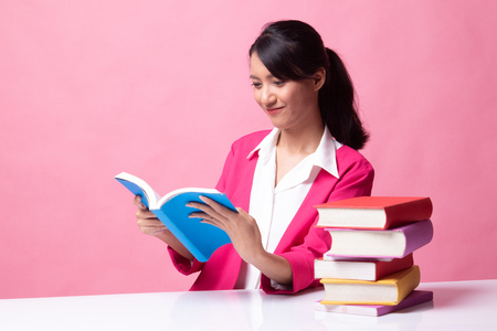 Young Asian woman read a book with books on table on pink background