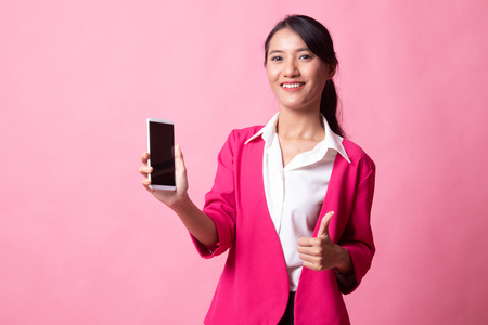 Young Asian woman show thumb up  with mobile phone on pink background Banque d'images