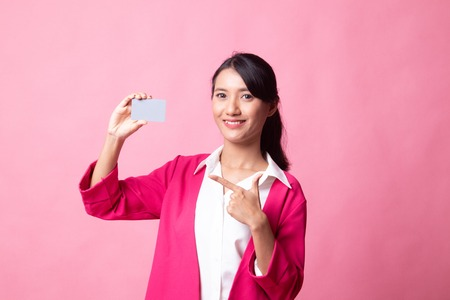 Young Asian woman point to a blank card on pink background 版權商用圖片