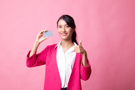 Young Asian woman thumbs up with a blank card on pink background 版權商用圖片 - 122814846