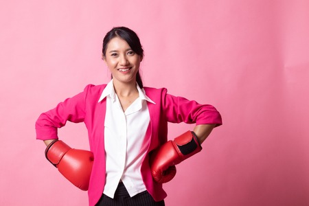 Young Asian woman with red boxing gloves on pink background Banco de Imagens