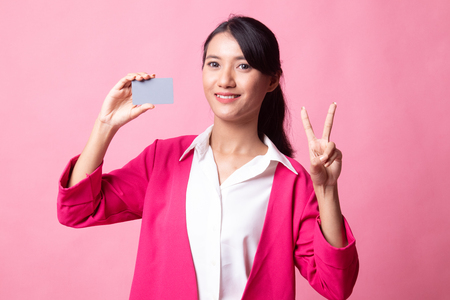 Young Asian woman show Victory with a blank card on pink background 版權商用圖片 - 122815222