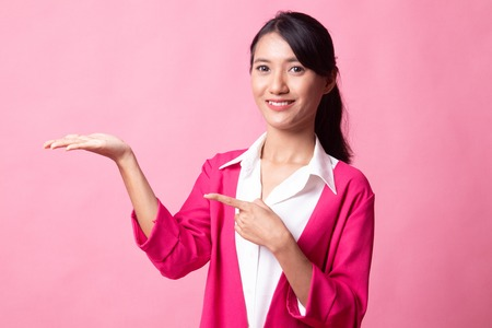 Beautiful young Asian woman point to palm hand on pink background