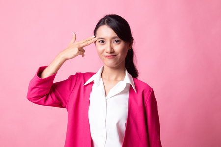 Beautiful young Asian woman holding fingers in gun gesture on pink background