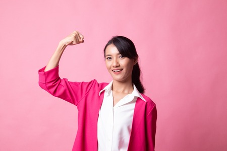 Beautiful young Asian woman flex bicep on pink background