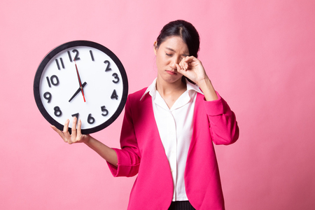 Sleepy young Asian woman with a clock in the morning on pink background