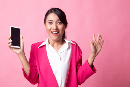 Young Asian woman with mobile phone on pink background 版權商用圖片