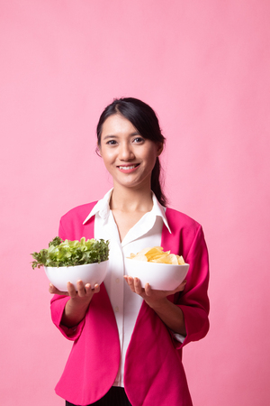 Young Asian woman with potato chips and salad on pink background