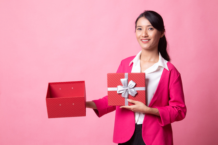 Young Asian woman open a golden gift box on pink background Stok Fotoğraf