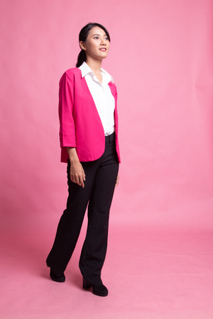 Full body of beautiful young asian woman walking on pink background 写真素材