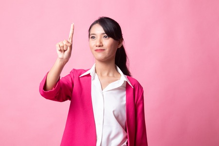 Asian woman touching the screen with her finger on pink background 版權商用圖片 - 122815367