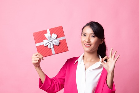 Young Asian woman show OK with a gift box on pink background Stock Photo - 122815369