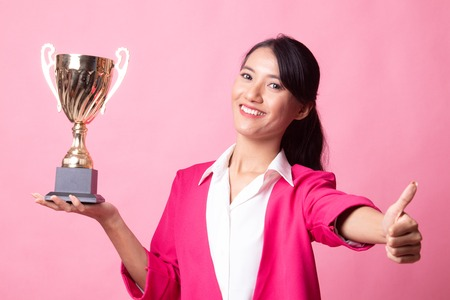 Successful young asian woman holding a trophy show thumb up on pink background