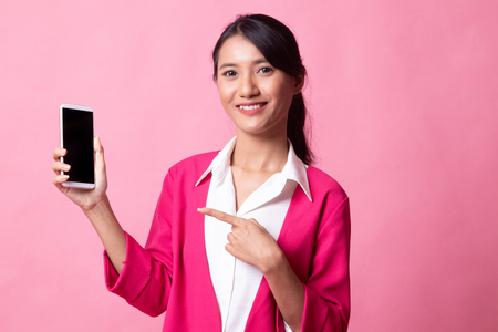 Young Asian woman point to mobile phone on pink background