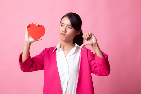 Asian woman thumbs down with red heart on pink background