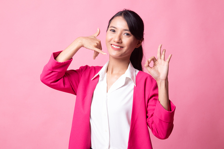 Young Asian woman show with phone gesture and OK sign on pink background 版權商用圖片 - 122816916