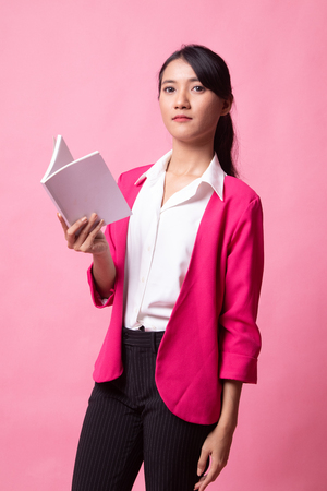 Young Asian woman read a book on pink background