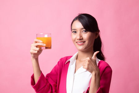 Young Asian woman thumbs up drink orange juice on pink background