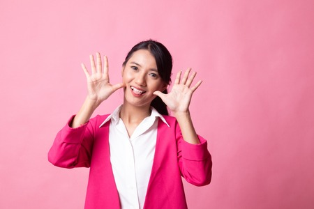 Young Asian woman sticking her  tongue out on pink background 版權商用圖片