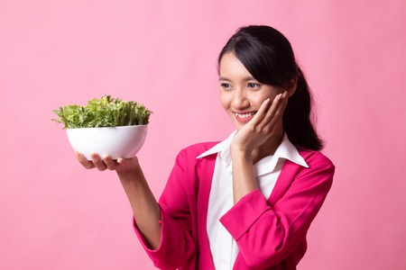 Healthy Asian woman with salad on pink background