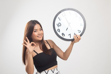 Young Asian woman show OK with a clock on white background Foto de archivo