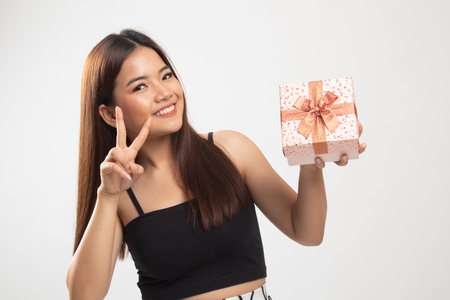 Young Asian woman show Victory sign with a gift box on white background 版權商用圖片 - 122817114